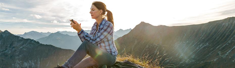 Frau mit Smartphone in den Bergen